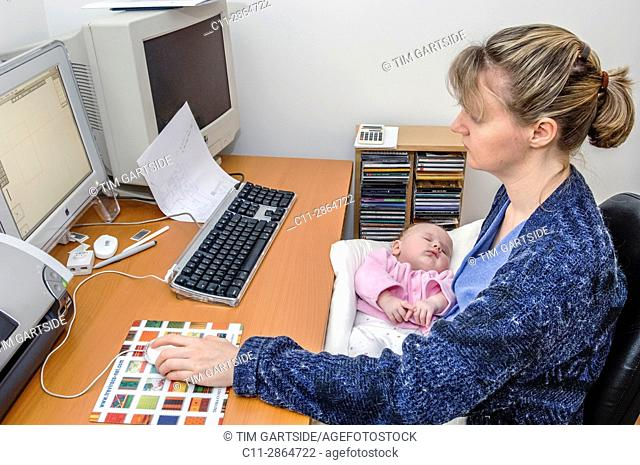 mother working at computer holding newborn baby