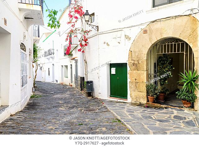 Whitewashed bougainvillea covered buildings and old town cobble streets of Cadaqués Town, Costa Brava, Spain