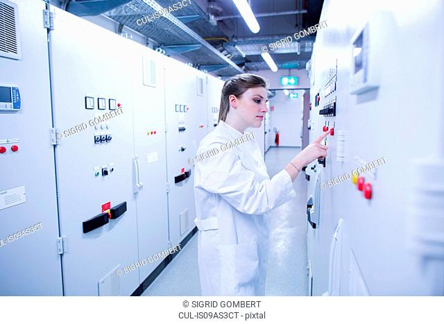 Young female scientist pressing button on machine control panel in technical room