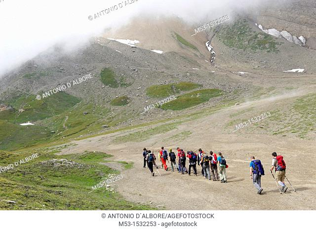 A group of hikers in single line formation cross the plateau called Piano dei Camosci, Lepontine Alps  Formazza  Italy