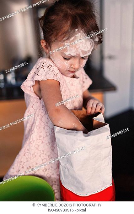 Messy girl in kitchen reaching into bag of flour