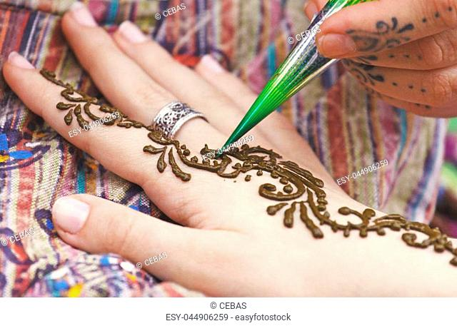 Artist painting traditional indian henna tattoo on woman hand, closeup picture, focus on mehndi artwork