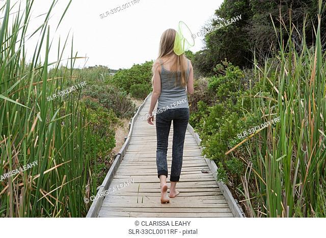 Girl carrying net on wooden walkway