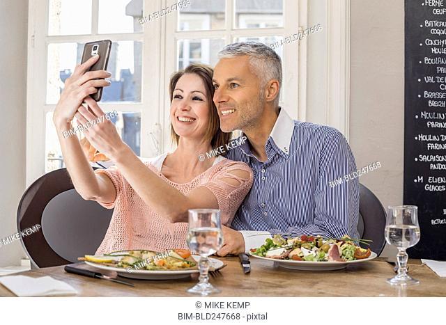 Caucasian couple posing for cell phones selfie in restaurant