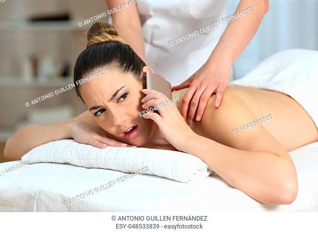 Stressed woman calling on phone receiving a massage in a spa salon