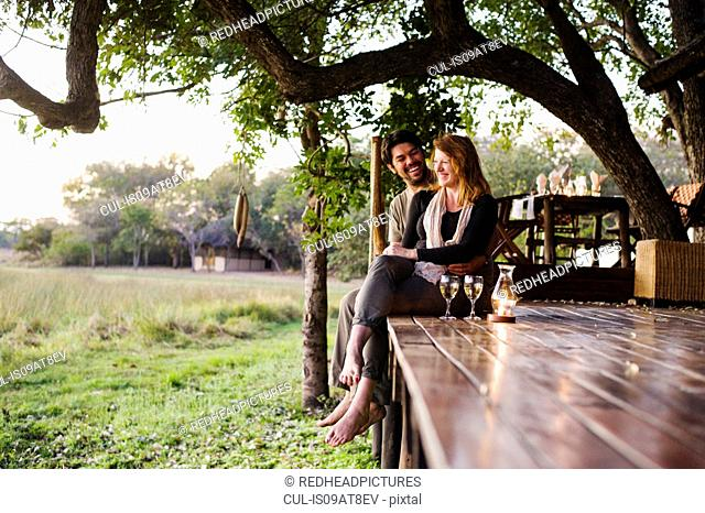 Couple relaxing at safari lodge, Kafue National Park, Zambia