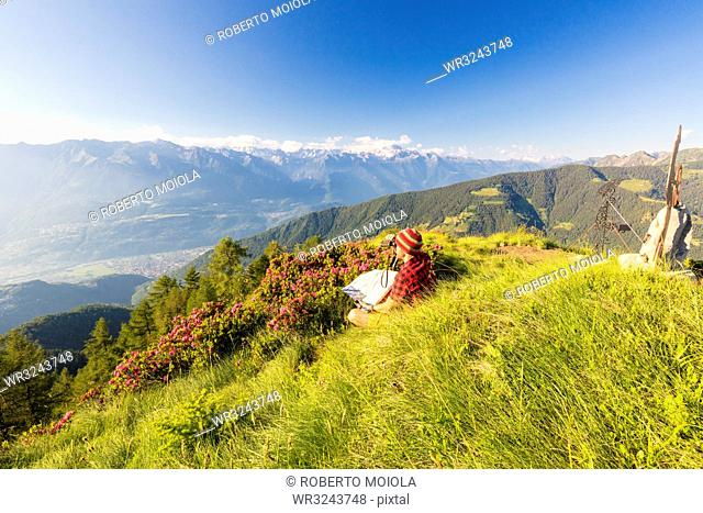 Hiker with binoculars and map looks towards Rhaetian Alps and Monte Disgrazia from Pizzo Berro, Bitto Valley, Lombardy, Italy, Europe
