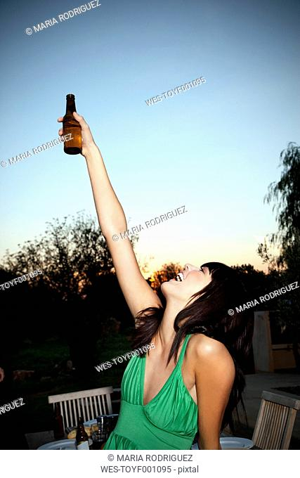 Happy young woman lifting a beer at sunset