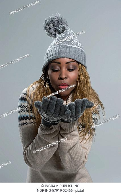 Christmas Girl. Winter woman Blowing from arms something