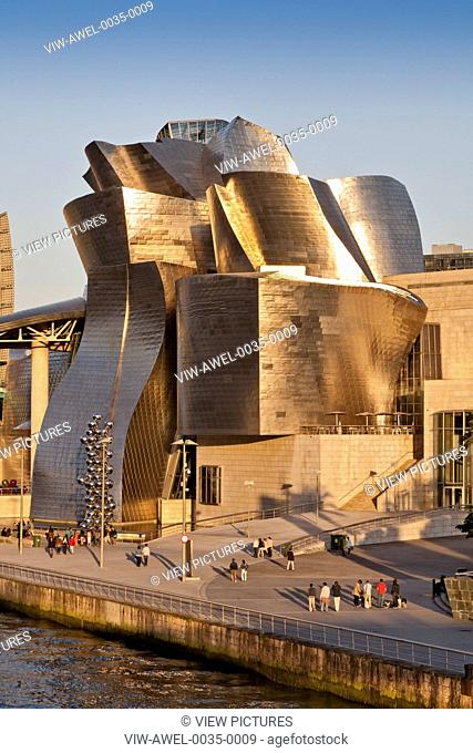 Guggenheim Museum Bilbao, Bilbao, Spain. Architect: Frank Gehry, 1997. General view of riverside elevation with late afternoon sun