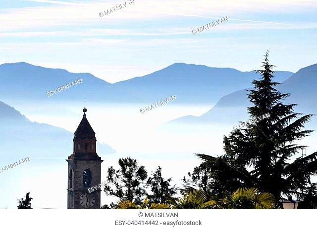 Church tower and a tree close to an alpine lake with fog and mountains