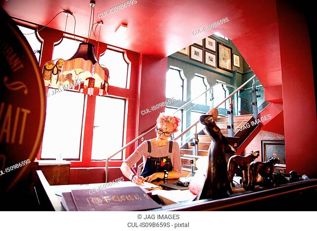 Quirky woman working at high counter at bar and restaurant, Bournemouth, England