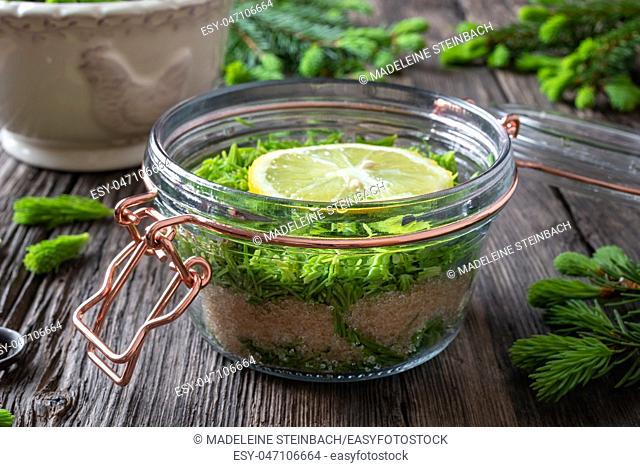 A jar filled with young spruce tips, lemon and cane sugar, to prepare homemade syrup against cough