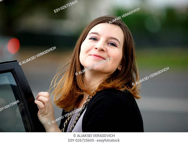 Young woman with long hair posing in the street, looking at the camera and smiling. Shallow depth of field. Focus on the model's face