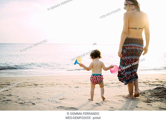 Thailand, Koh Lanta, back view of baby girl and mother on the beach by sunset