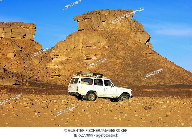 Jeep crosses the Hamada desert in the Acacus Mountains, Libya