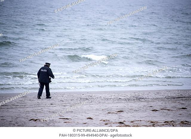 13 March 2018, Germany, Hiddensee: Island police officer Martina Dominik on duty despite the rain at the beach on the Baltic Sea island of Hiddensee