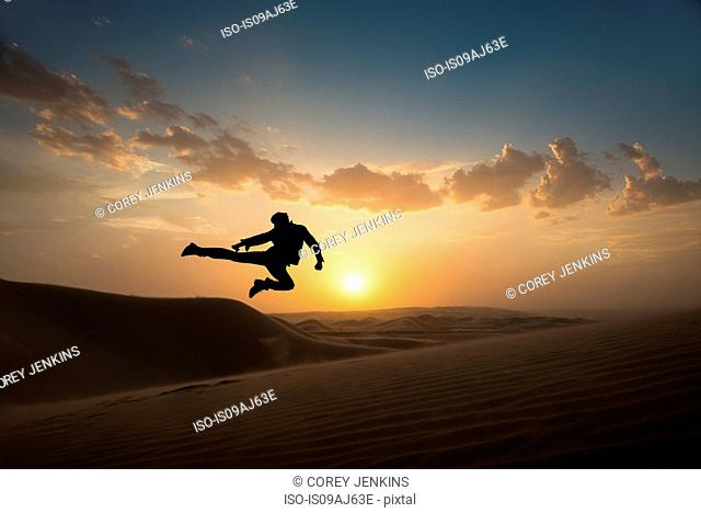 Man jumping mid air, Glamis sand dunes, California, USA