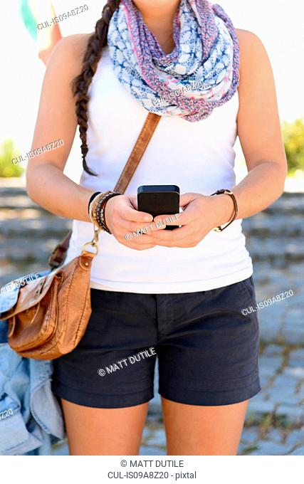 Close up of young female standing in street using smartphone