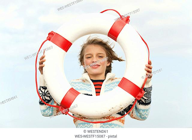 Germany, North Sea, St.Peter-Ording, Boy 8-9 holding life saver at beach, smiling, portrait