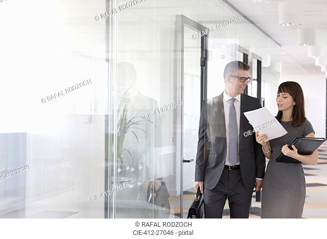 Businessman and businesswoman discussing report in office corridor