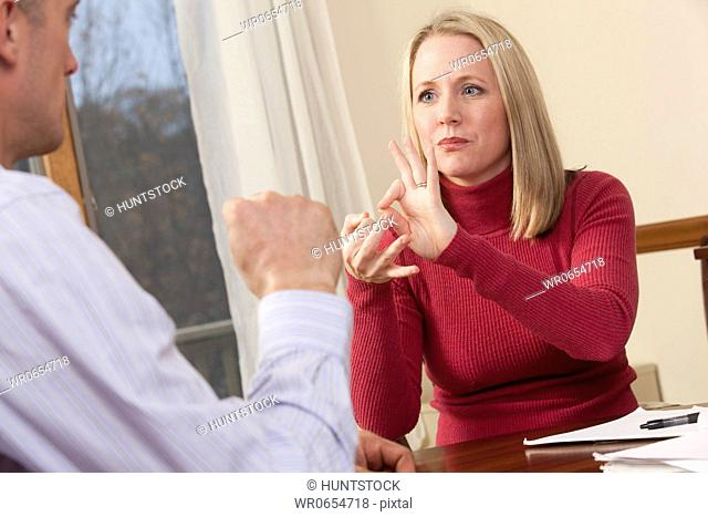 Woman signing the word interpreter in American Sign Language while communicating with a man