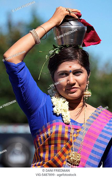 A Tamil Hindu devotee carries a metal pot containing milk and honey on her head during the Ayyappan chariot festival in Ontario, Canada