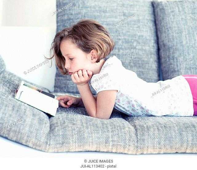 Young girl reading on sofa