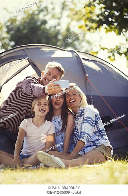Happy family taking selfie with camera phone outside sunny campsite tent