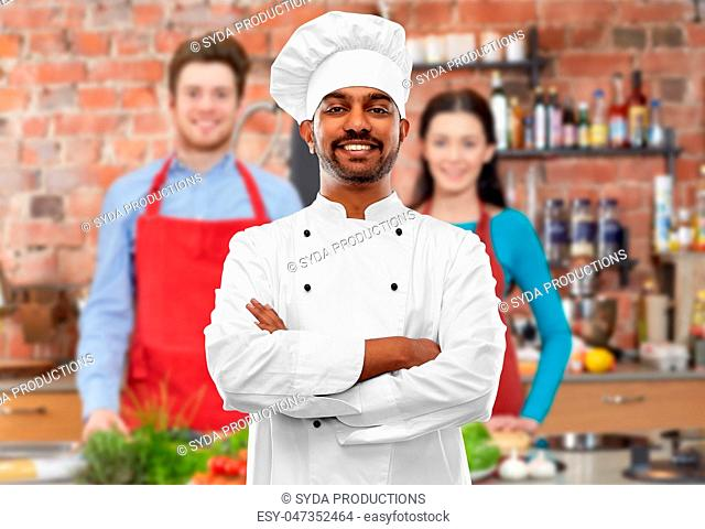 happy male indian chef in toque at cooking class