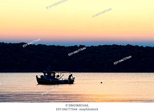 Fisherman working at sunset in Pagasetic gulf, Greece