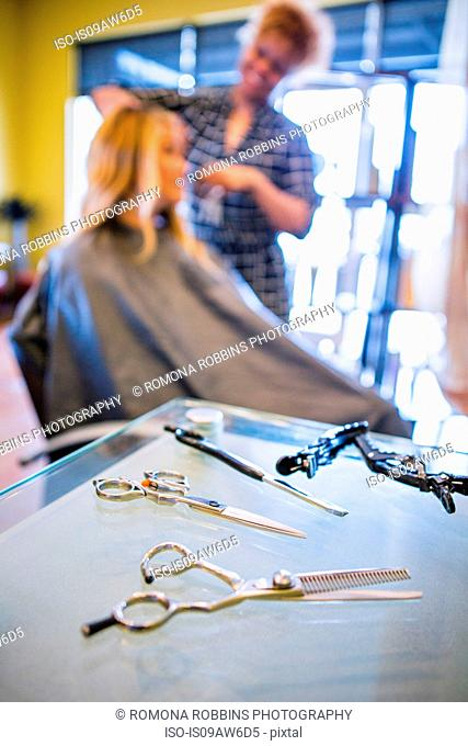 Stylist cutting woman's hair in hair salon, focus on scissors in foreground