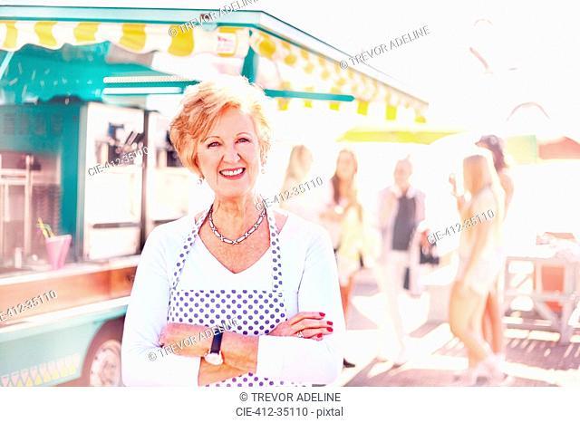Portrait smiling senior female business owner outside food cart