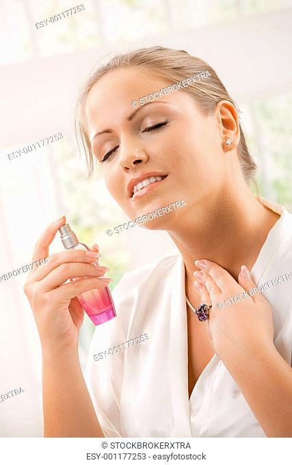 Woman applying perfume