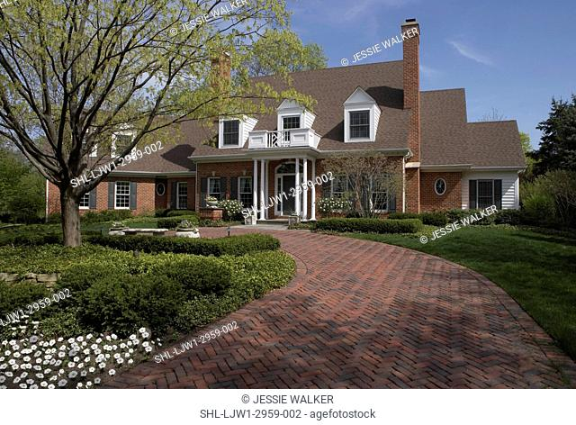 Exterior: Red brick house with red brick curved driveway. Green shutters, two chimneys, portico with white columns, dormer windows, attached garage, flowers