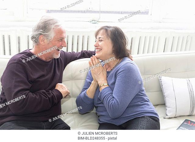 Older couple sitting on sofa and laughing