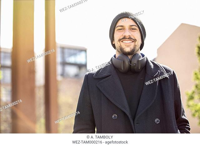 Portrait of smiling young man with headphones wearing wool cap and black pullover