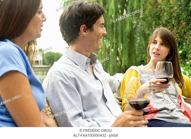 Friends relaxing outdoors with glass of wine
