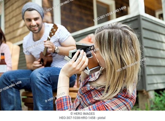 Woman photographing man playing guitar with vintage camera