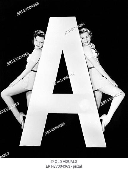 Two women with huge letter A All persons depicted are not longer living and no estate exists Supplier warranties that there will be no model release issues