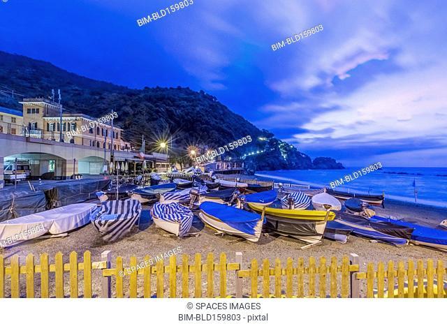 Canoes docked on beach under Monterosso al Mare cityscape, La Spezia, Italy