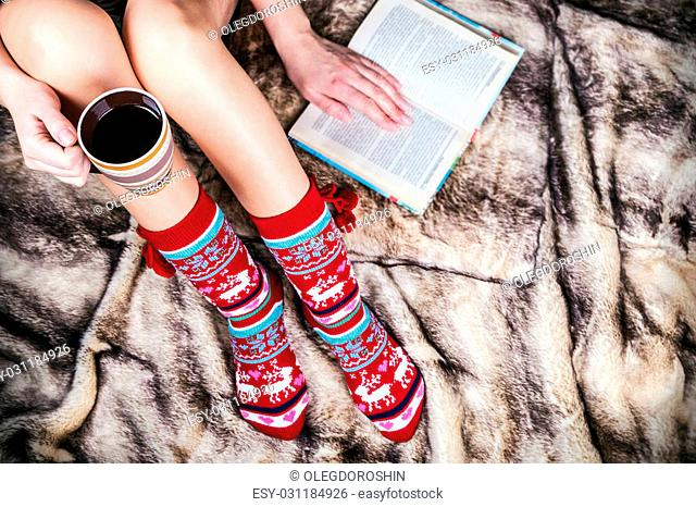 female legs in Christmas socks with a book and a cup of coffee. artificial fur on the floor