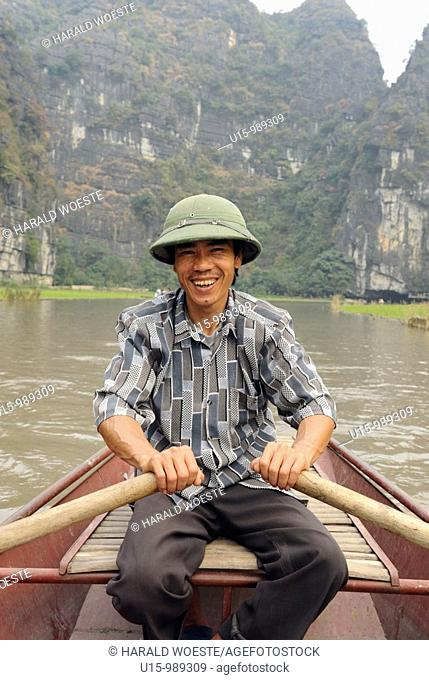 Asia, Vietnam, Tam Coc near Ninh Binh  Boat trip at Tam Coc Three Caves  To visit the Three Caves Tam Coc tourists are punted in metal boats along the watery...