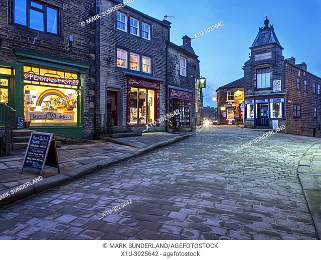Lights coming on along the cobbled Main Street in Haworth Village at dusk West Yorkshire England