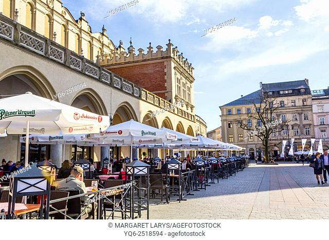 Tourists having meal and resting in the garden restaurant outside Cloth Hall in Krakow, Old Town, Poland, Europe