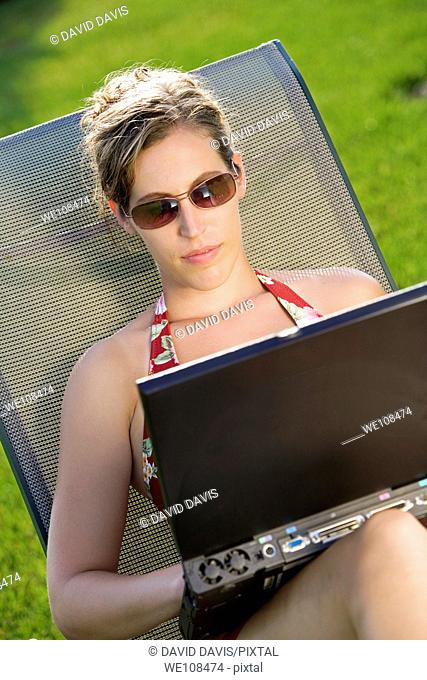 Woman in mid 20s sunbathing and working on a laptop computer