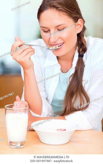 Portrait of a calm woman having breakfast in her kitchen