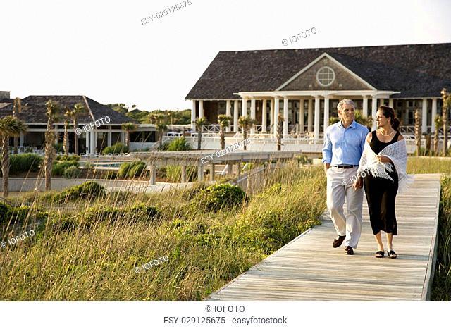 Caucasian mid-adult couple walking on walkway near beach home