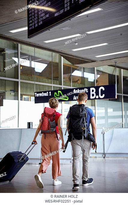 Rear view of couple walking at the airport