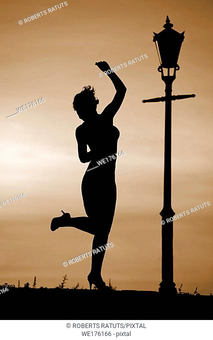 Silhouette of women dancing at sunset by lantern